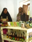 Shop keepers with syrups, treats, soaps and place mats - Dada:Moto Hurumzi Str. 416